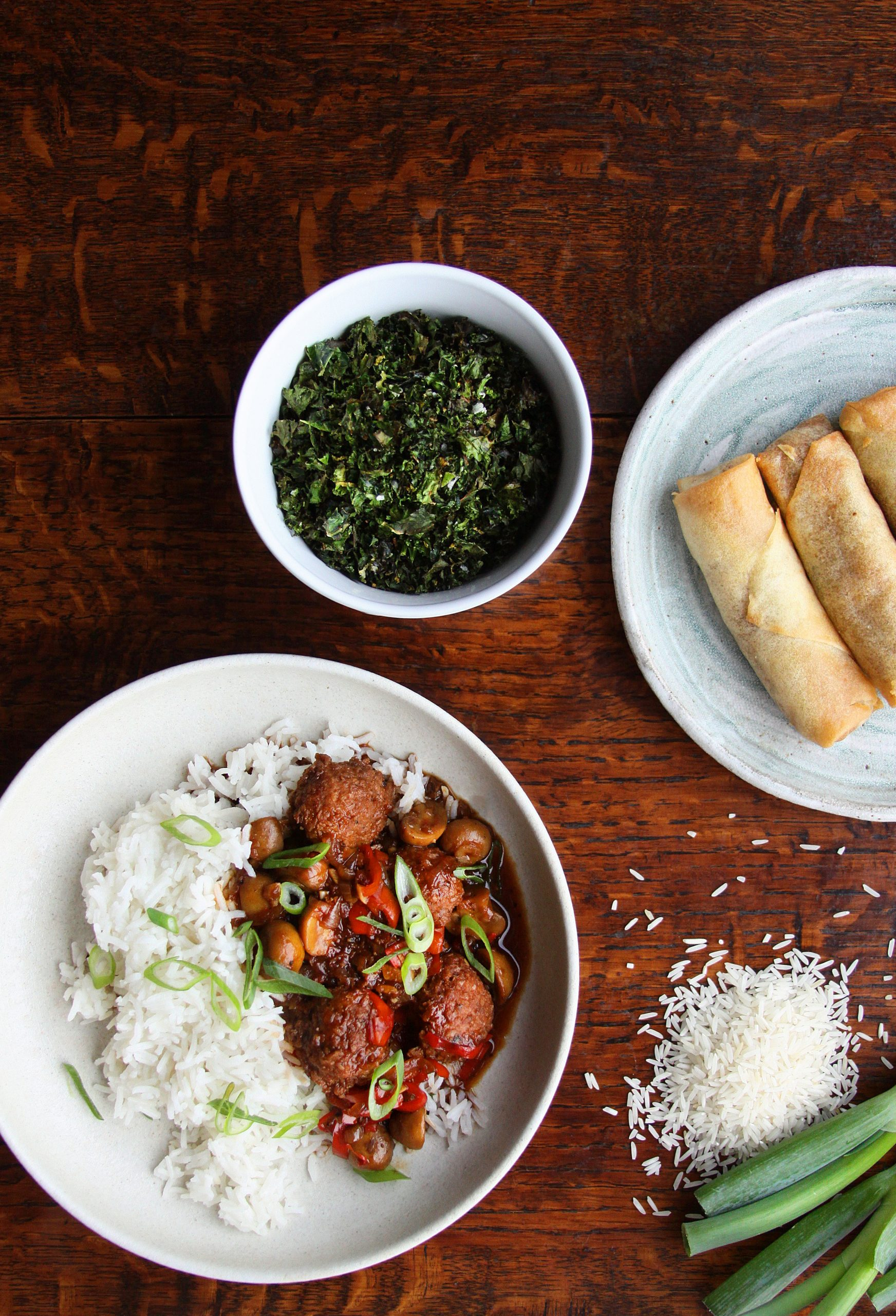 Table setting that includes black pepper vegan meatballs and rice, crispy kale and spring rolls